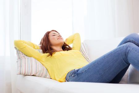 relajado: concepto de hogar y la felicidad - sonriente mujer joven tumbado en el sof� en casa