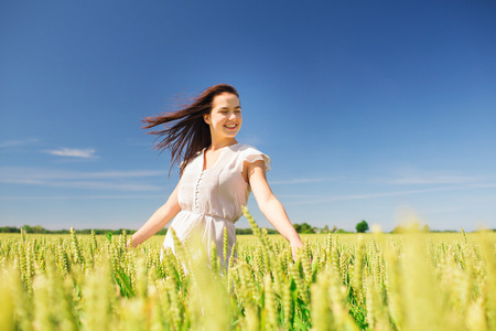 happiness, nature, summer, vacation and people concept - smiling young woman on cereal field photo