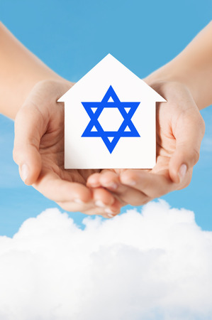 religion, judaism and charity concept - close up of woman hands holding house with star of david over blue sky with white cloud background photo