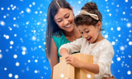 little girl surprised: christmas, holidays, celebration, family and people concept - happy mother and child girl with gift box over blue snowy background Stock Photo