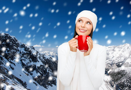 happiness, winter holidays, christmas, beverages and people concept - smiling young woman in white warm clothes with red cup over snowy mountains background photo