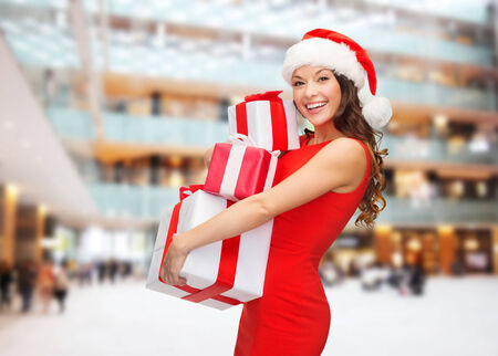 christmas, holidays, celebration and people concept - smiling woman in red dress with gift boxes over shopping center background photo