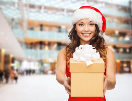 christmas, holidays, celebration and people concept - smiling woman in red dress with gift box over shopping center background photo