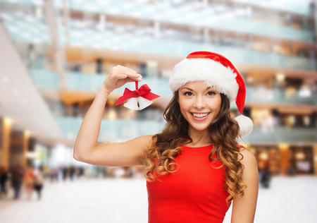 christmas, holidays, winter, happiness and people concept - smiling woman in santa helper hat with jingle bells over shopping center background photo