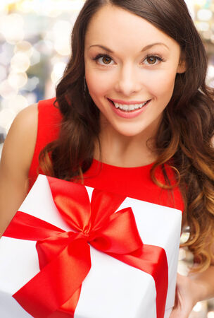 gift giving: christmas, holidays, celebration and people concept - close up of smiling woman with gift box over lights background