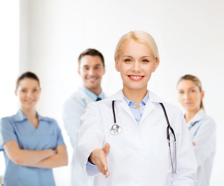 healthcare and medicine concept - smiling female doctor with stethoscope ready to shake hands photo