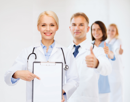 healthcare and medicine concept - smiling female doctor pointing finger to clipboard and blank page with team on the back photo