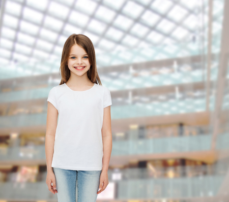 blank center: advertising, childhood, consumerism and people - smiling little girl in white blank t-shirt over shopping center background