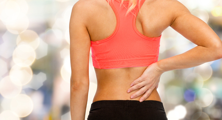 pain: fitness, healthcare and medicine concept - close up of sporty woman touching her back
