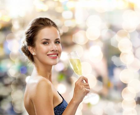 partij, dranken, vakantie, luxe en viering concept - glimlachende vrouw in avondjurk met een glas mousserende wijn over lichten achtergrond Stockfoto
