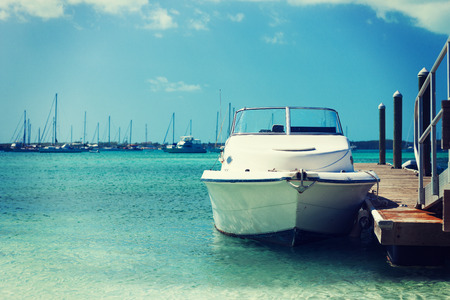 vacation, travel and sea concept - white boat at blue sea
