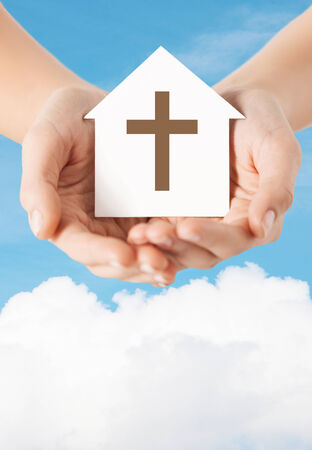 house of prayer: religion, christianity and charity concept - close up of woman hands holding paper house with christian cross symbol over blue sky with white cloud background