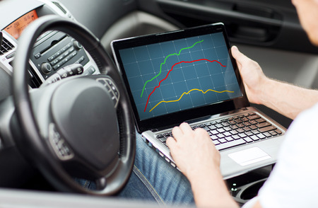 transportation, technology, people and vehicle concept - close up of man using laptop computer in car Stock Photo
