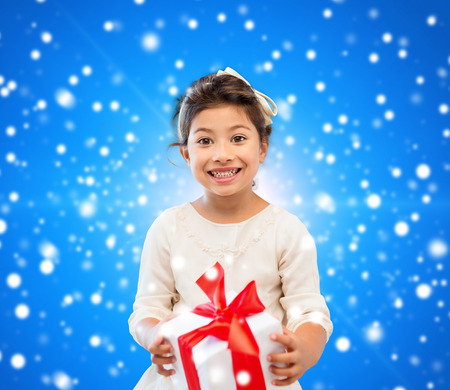 holidays, presents, christmas, childhood and people concept - smiling little girl girl with gift box over blue lights background photo