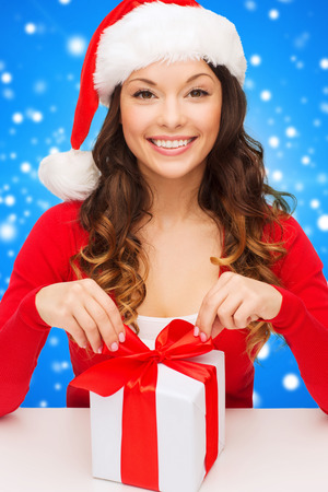 christmas, holidays, celebration and people concept - smiling woman in santa helper hat with gift box over blue snowy background photo