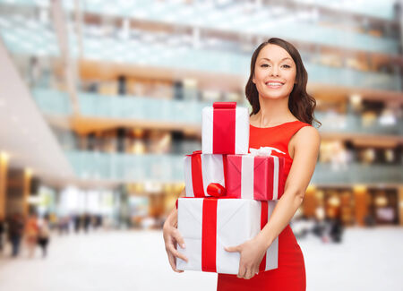 christmas, holidays, valentines day, celebration and people concept - smiling woman in red dress with gift boxes over shopping center background photo