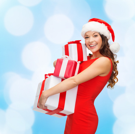 christmas, holidays, celebration and people concept - smiling woman in red dress with gift boxes over blue lights background photo