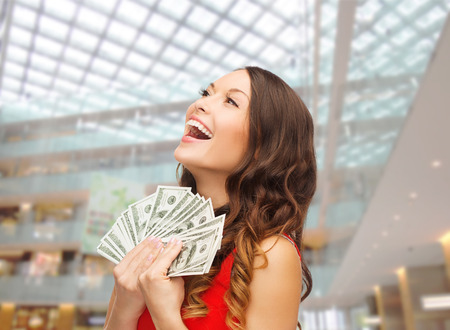 christmas, x-mas, shopping, banking and people concept - smiling woman in red dress with us dollar money over shopping centre background photo