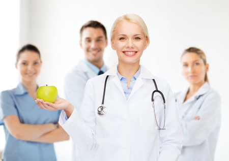 healthcare and medicine concept - smiling female doctor with stethoscope and green apple photo