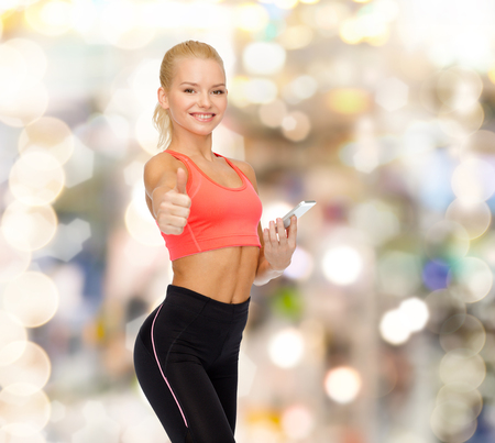 sport, fitness, technology, internet and healthcare concept - smiling sporty woman with smartphone showing thumbs up photo