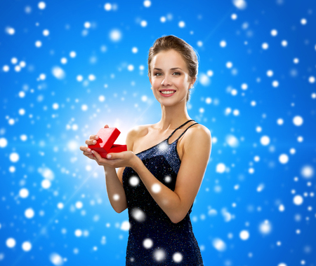 winter holidays, christmas, presents, luxury and happiness concept - smiling woman in dress holding red gift box over blue snowy background photo