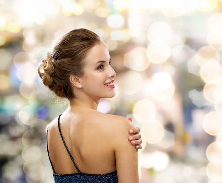 people, holidays and glamour concept - smiling woman in evening dress over black background over lights background from back