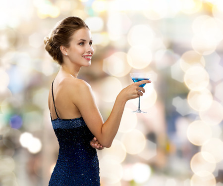 party, drinks, holidays, luxury and celebration concept - smiling woman in evening dress holding cocktail over lights background Foto de archivo
