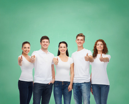 approvement: advertising, friendship, education, school and people concept - group of smiling teenagers in white blank t-shirts showing thumbs up over green board background