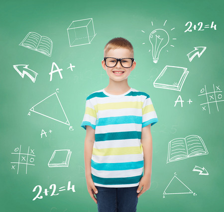 vision, education, childhood and school concept - smiling little boy in eyeglasses over green board with doodles background photo
