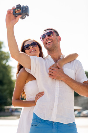 taking a wife: love, wedding, summer, dating and people concept - smiling couple wearing sunglasses making selfie with digital camera in park