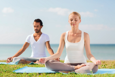 fitness, sport, friendship and lifestyle concept - smiling couple making yoga exercises sitting on mats outdoors photo