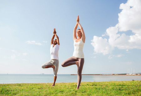 yoga man: fitness, sport, friendship and lifestyle concept - smiling couple making yoga exercises outdoors