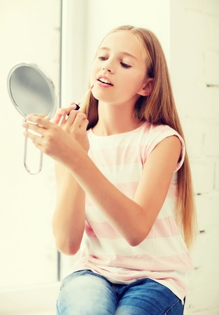 puberty: adolescence, beauty, makeup, happy people concept - teenage girl with lip gloss and mirror