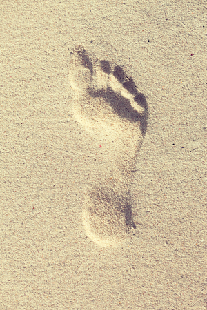 sandy feet: travel, adventure and beach concept - footprint on sand