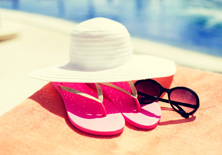 weekend activities: beach, summer, vacation and accessories concept - close up of hat, flip-flops and sunglasses at pool