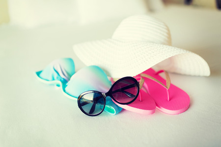 vacation, holiday and travel concept - close-up of bikini top, straw hat, flip-flop and sunglasses on hotel bed photo