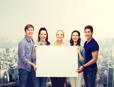 education and people concept - group of standing smiling students with white blank board photo