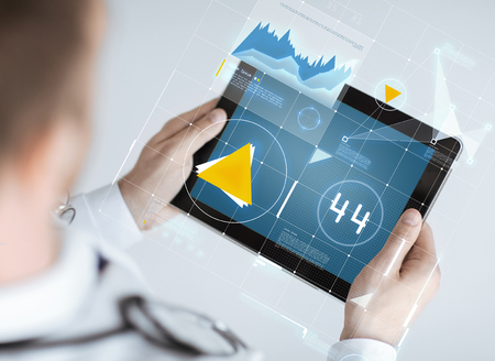 medicine, technology and people concept - close up of doctor holding tablet pc with graph on screen photo