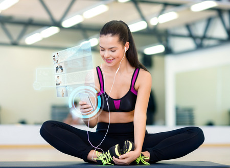 fitness, sport, training, technology and lifestyle concept - smiling young woman with smartphone and earphones in gym