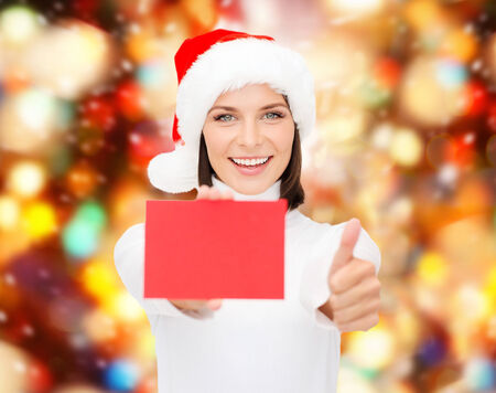 christmas, holdays, people, advertisement and sale concept - happy woman in santa helper hat with blank red card showing thumbs up gesture over lights background photo