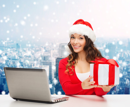 christmas, holidays, technology and people concept - smiling woman in santa helper hat with gift box and laptop computer over snowy city snowing background photo