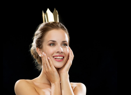 people, holidays, royalty and glamour concept - laughing woman wearing golden crown over black background photo