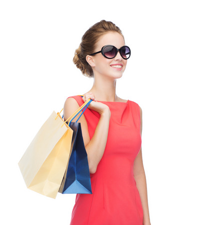 consumerism: shopping, sale, christmas and holiday concept - smiling elegant woman in red dress and sunglasses with shopping bags Stock Photo