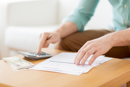 account: savings, finances, economy and home concept - close up of man with calculator counting money and making notes at home
