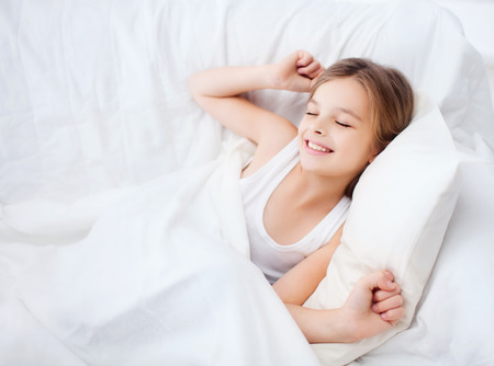 health, beauty and childhood concept - smiling girl child waking up in bed at home Imagens