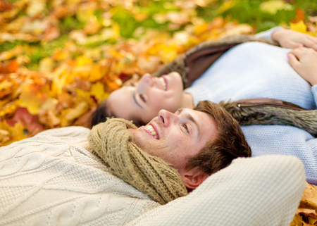 wool: love, relationship, season, family and people concept - close up of smiling couple lying in autumn park