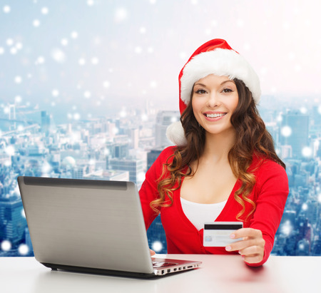 christmas, holidays, technology and shopping concept - smiling woman in santa helper hat with credit card and laptop computer over snowy city background photo