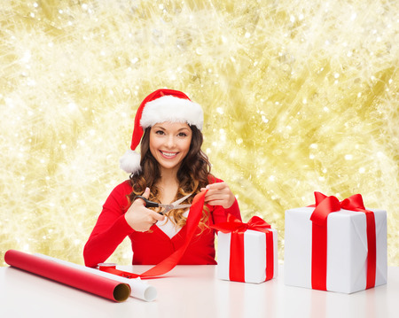 christmas, holidays, celebration, decoration and people concept - smiling woman in santa helper hat with scissors packing gift box over yellow lights background photo