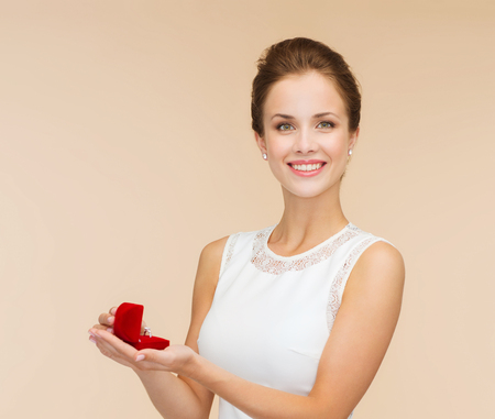 wedding, love, engagement and happiness concept - smiling woman in white dress holding red gift box with diamond ring over beige background photo