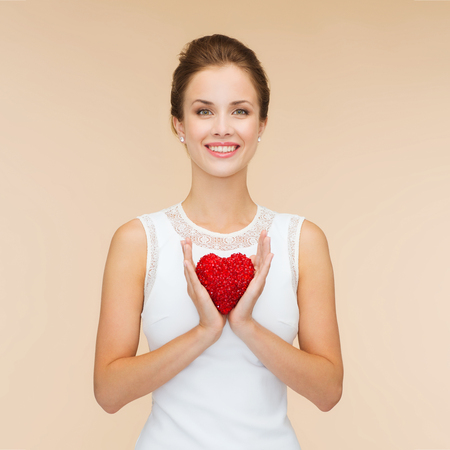 happiness, health, charity and love concept - smiling woman in white dress with red heart over beige background photo